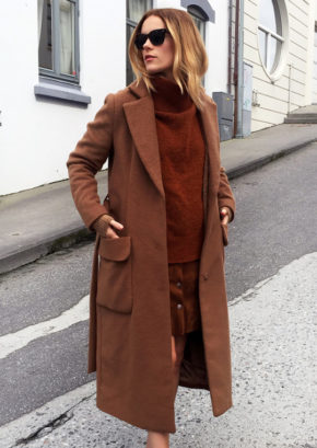 Sara Strand goes all out in terracotta, wearing an authentic rust coloured coat, pullover and skirt. Outfit: Lindex, Sneakers: Adidas by Stella McCartney.