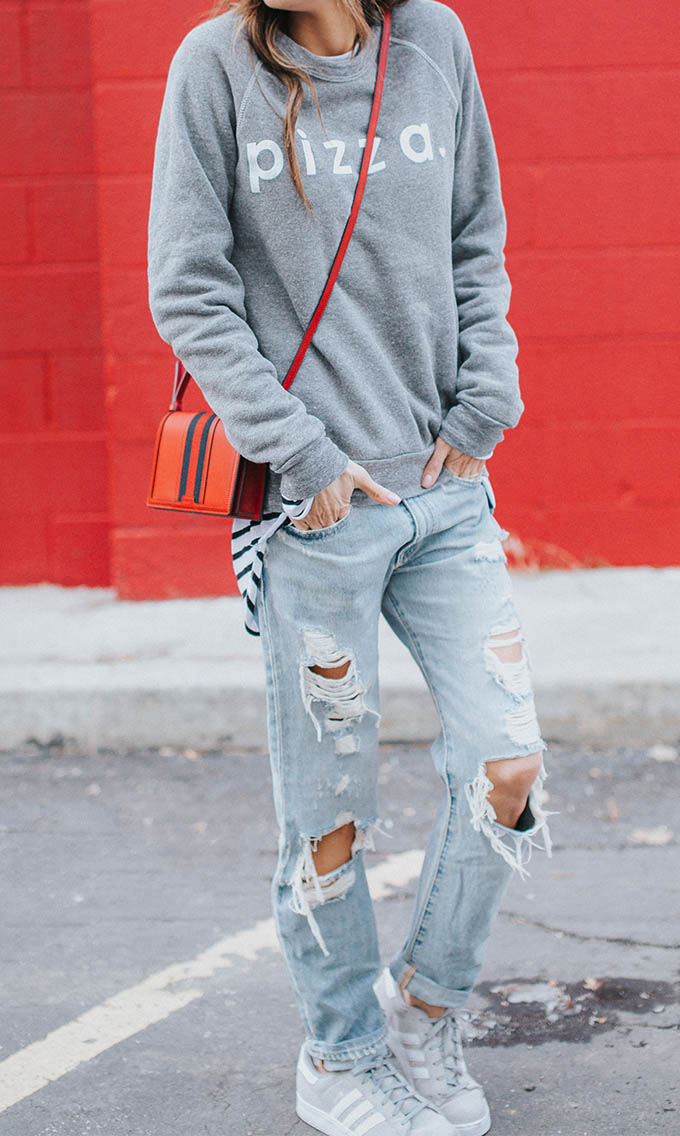 Christine Andrew is rocking the tomboy style, pairing a cool grey graphic print sweater with a pair of destroyed jeans and adidas striped sneakers. This style is both ultra cute and achievable, and can be worn almost anywhere! Sweater: ILY, Jeans: Macy's, Sneakers: Adidas.