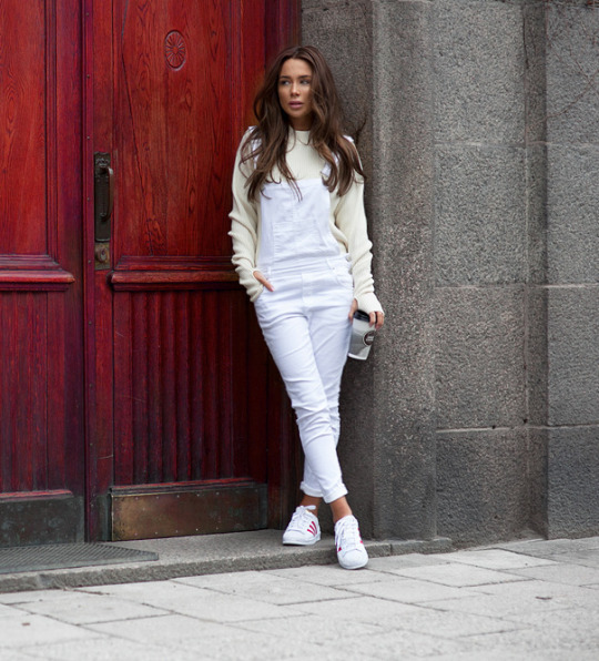 Dare to wear dungarees this season! Johanna Olsson is rocking this white piece, pairing it with simple white sneakers and a yellow sweater. Perfect all year round, this outfit is retro and cool! Brands not specified.