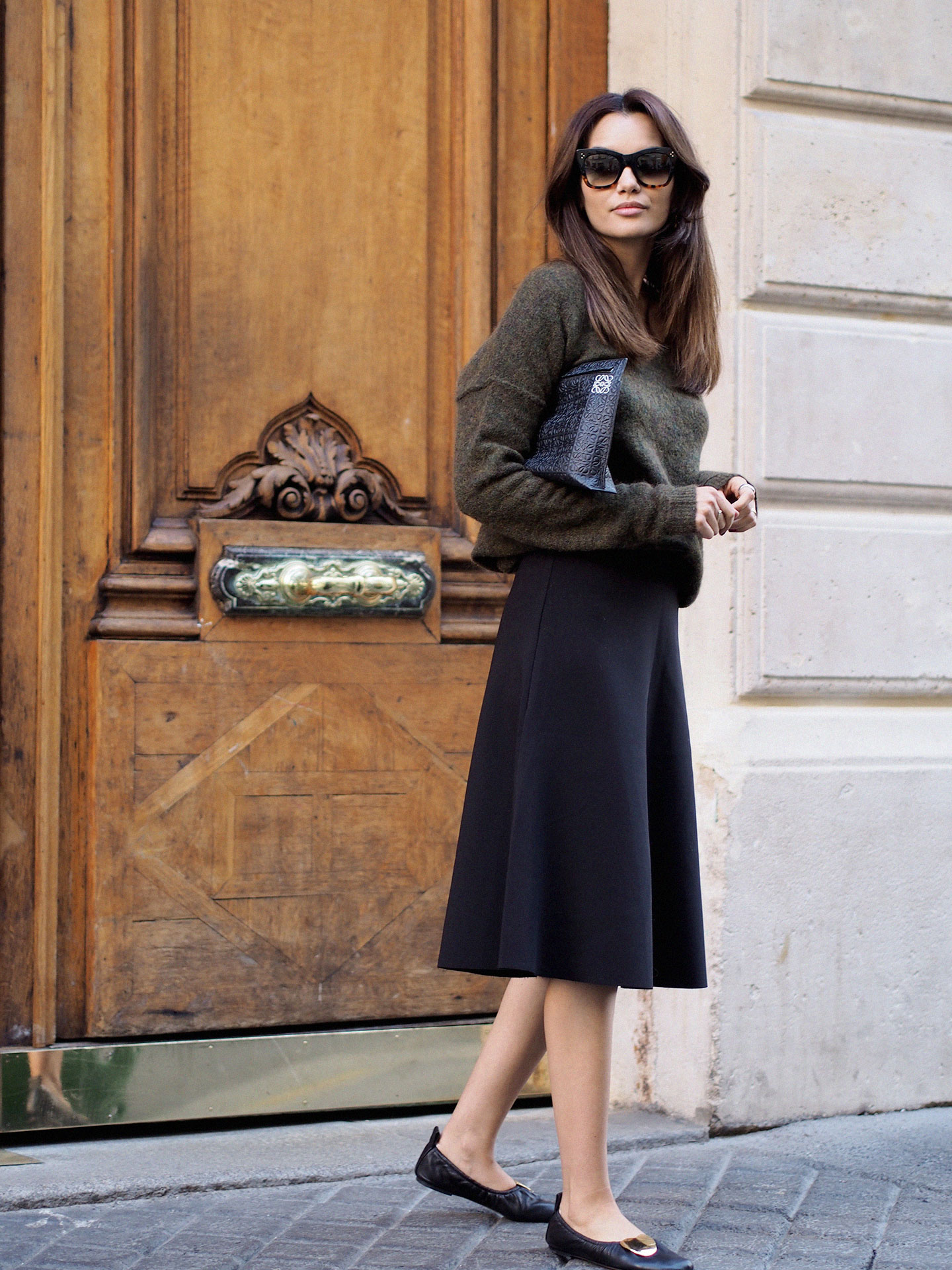 Funda Christophersen's cute fall outfit consists of a cropped knit sweater worn stylishly over a knee length black skirt and matched with vintage style flats. This look is smart and sophisticated, and suitable for any occasion. Sweater: Second Female, Skirt: Cos, Shoes: Celine, Bag: Loewe.
