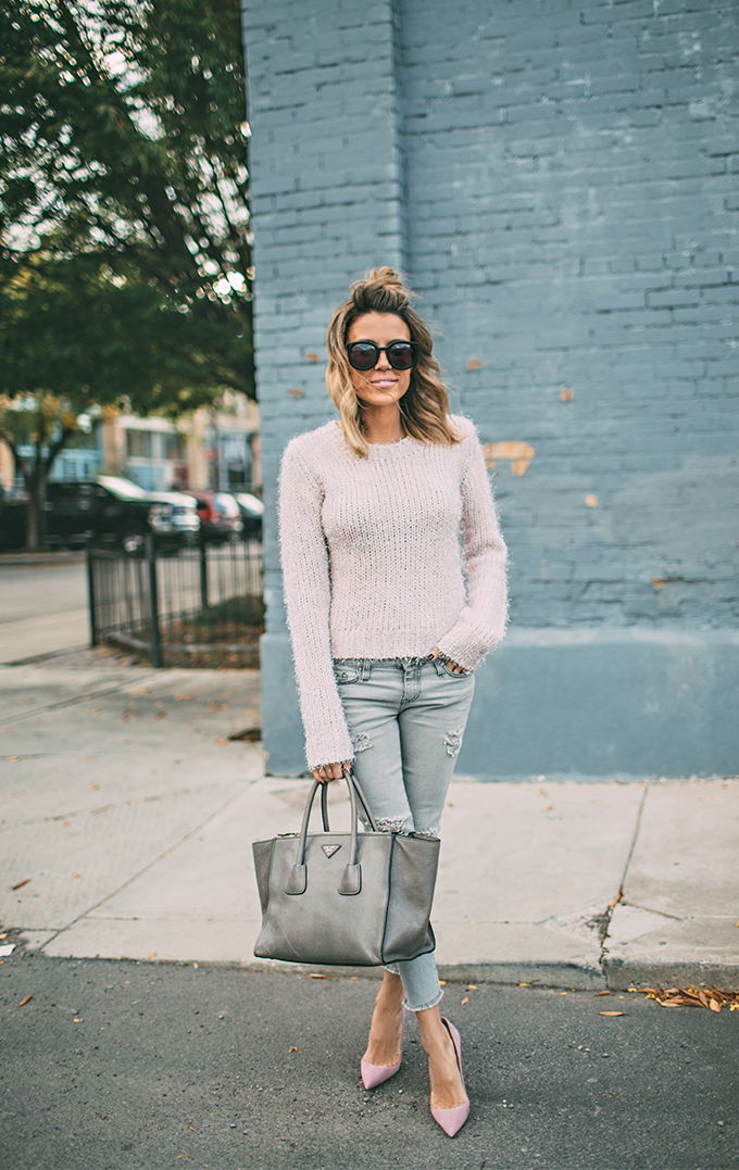 A pale blush knit piece such as this cute sweater from Ily Couture can create a casual but bright style, great for those winter mornings! Christine Andrew wears the look with distressed denim jeans and matching blush heels. Sweater: Ily Couture, Jeans: Neiman Marcus, Heels: Christian Louboutin.