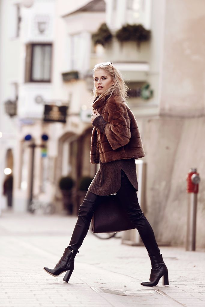 Caroline Daur is a vision in brown, rocking a pair of tight leather leggings, an oversized knit sweater, and a cute cropped faux fur jacket. Finish the look off with a pair of heeled ankle boots to recreate this look. Jacket: Hallhuber, Pullover: Bogner, Shoes: Zara, Sunglasses: Jimmy Choo, Bag - Aigner.