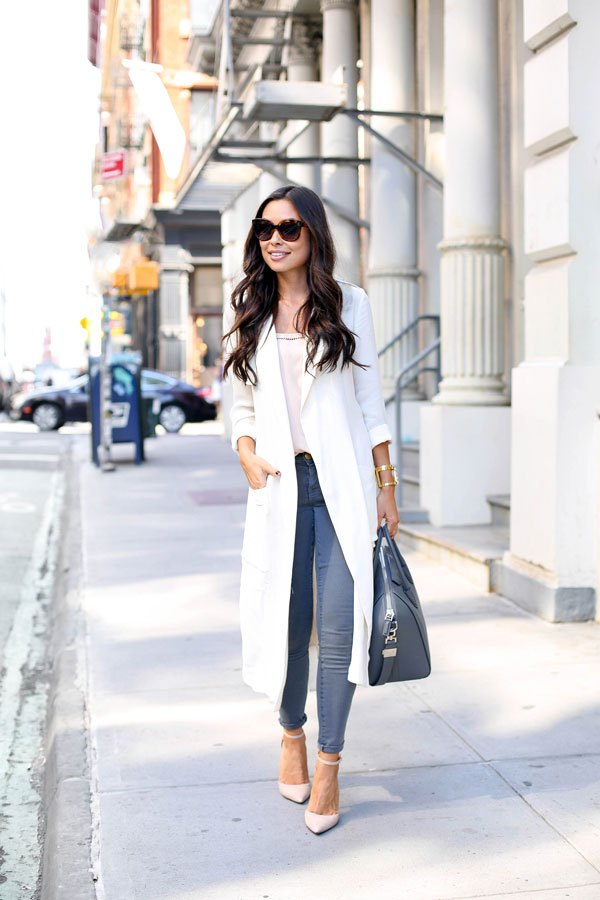 Dare to wear a white trench coat this fall! Kat Tanita demonstrates the elegance of this trend by wearing hers with skinny jeans, a leather bag, and pale pink heels to create a gorgeous fall look Tank Top: Equipment, Jeans: Elliott, Coat: Cynthia Vincent.