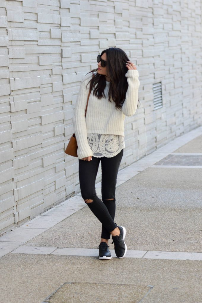 Federica L. is wearing a casual outfit consisting of distressed grey denim jeans, a lace blouse, and a cable knit white sweater. Federica finishes the look off with sneakers and shades.   Sweater: Pull & Bear, Blouse: Pop My Dress, Trousers: Zara, Bag: Elleme.