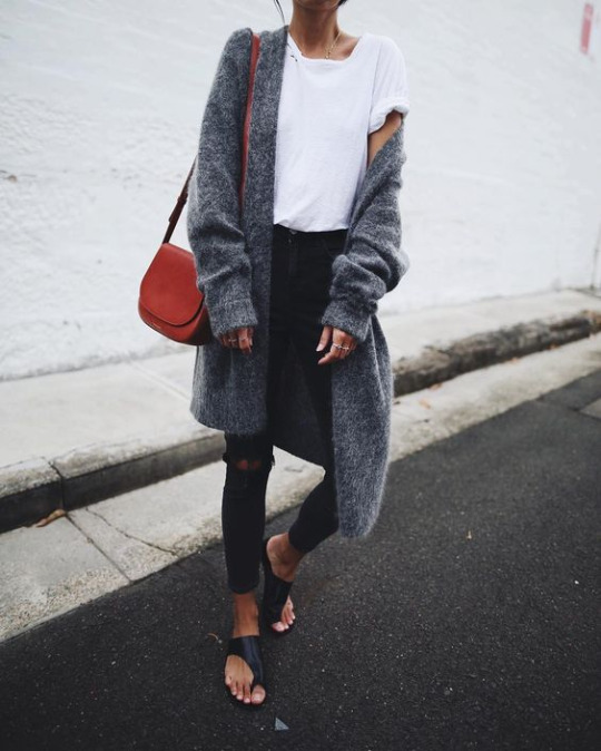 Andy is wearing a simple white tee with ripped black jeans and an oversized cashmere cardigan, creating an effortlessly casual look. She wears this look with open sandals and a miniature bag.  Jeans: Topshop, Cardi: Acne, Shoes: Atpa Atelier.