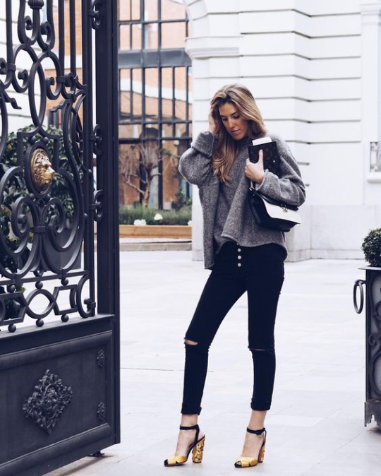 Carla Hinojosa is wearing distressed black jeans with an oversized grey sweater and statement heels for a sophisticated yet casual style.   Jumper: Zara, Shoes: Sebastian Milano.