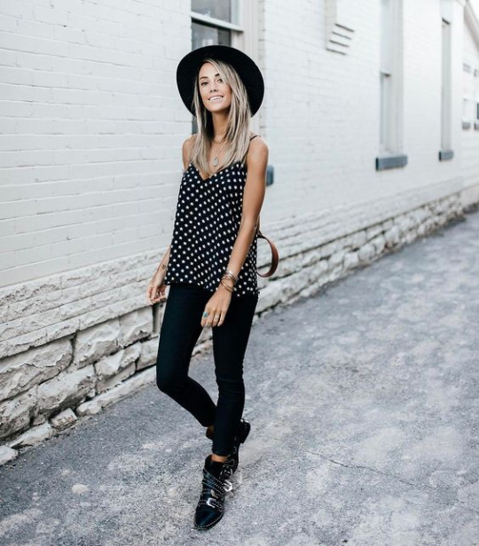 Meg wears a cute black and white polka dot cami with black skinnies for a smart causal style which we love. She accessorises this look with a wide brimmed fedora hat and pairs the overall style with chunky boots.   Shoes: Givenchy, Top: Revolve.