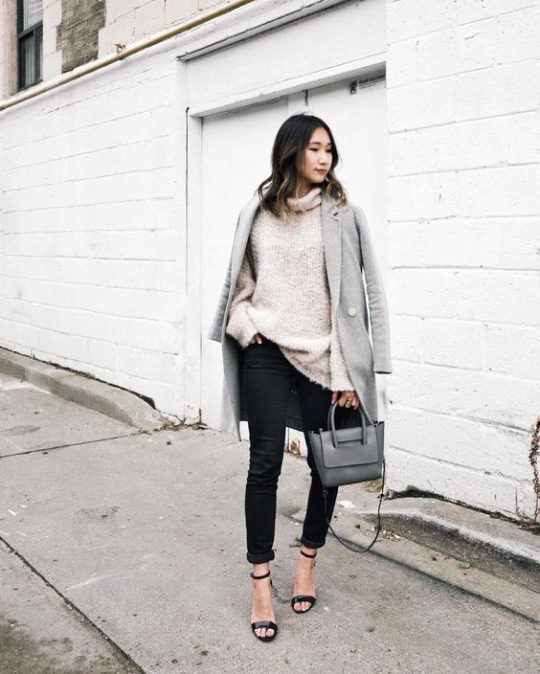 Tina Hu wears black jeans with an oversized beige knitted turtleneck, paired with a grey one-button overcoat and heeled sandals, in black. Tina accessorises this look with a simple marl grey mini bag. Sweater: Free People, Coat: Aritzia, Shoes: Aldo.