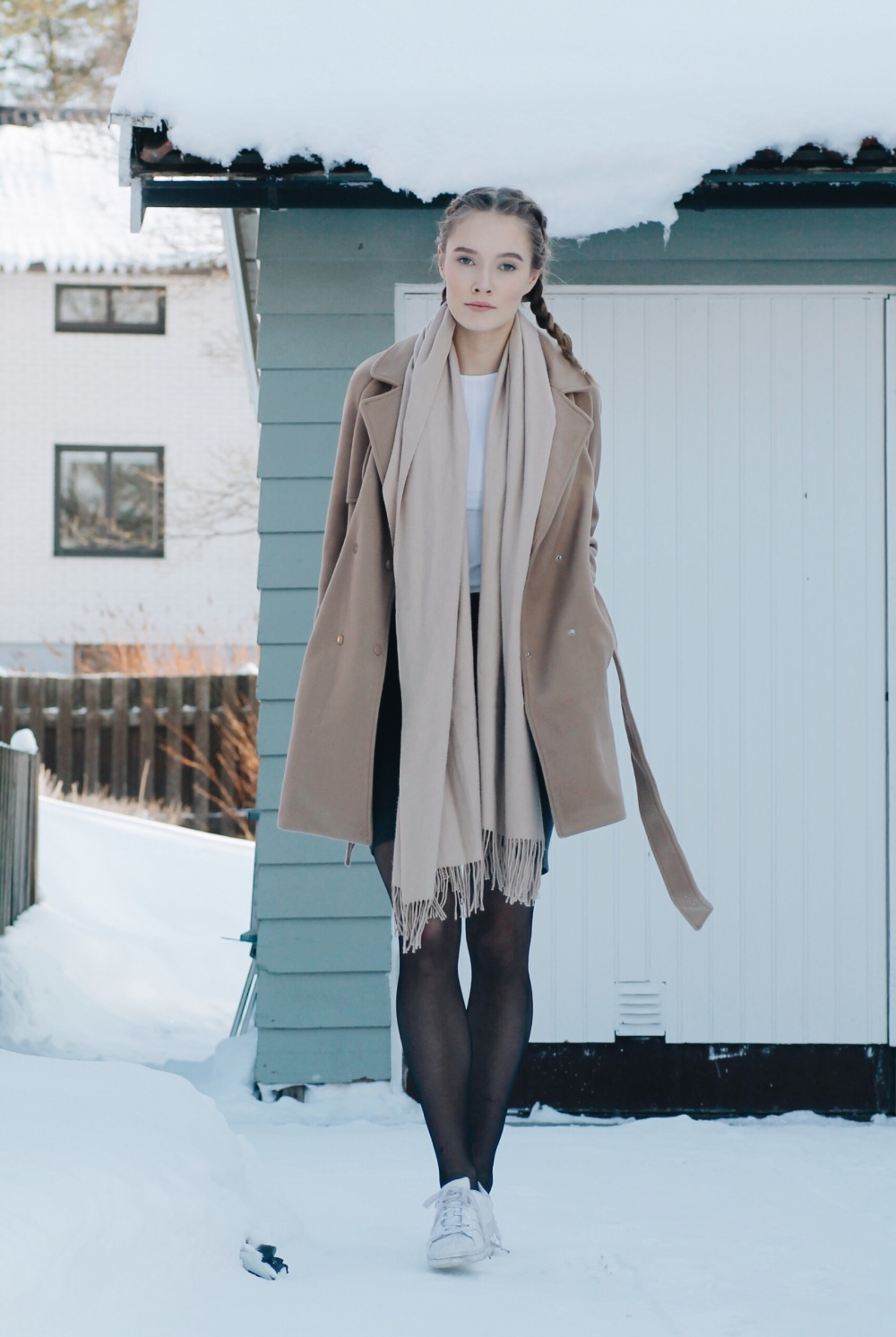 Petra Karlsson is a picture in beige, pairing a gorgeous beige overcoat with a matching scarf and a white tee for a fresh winter feel. Wear this look with a mini skirt and casual sneakers to steal Petra's style. Coat/Skirt: Shein, Top: Bikbok.