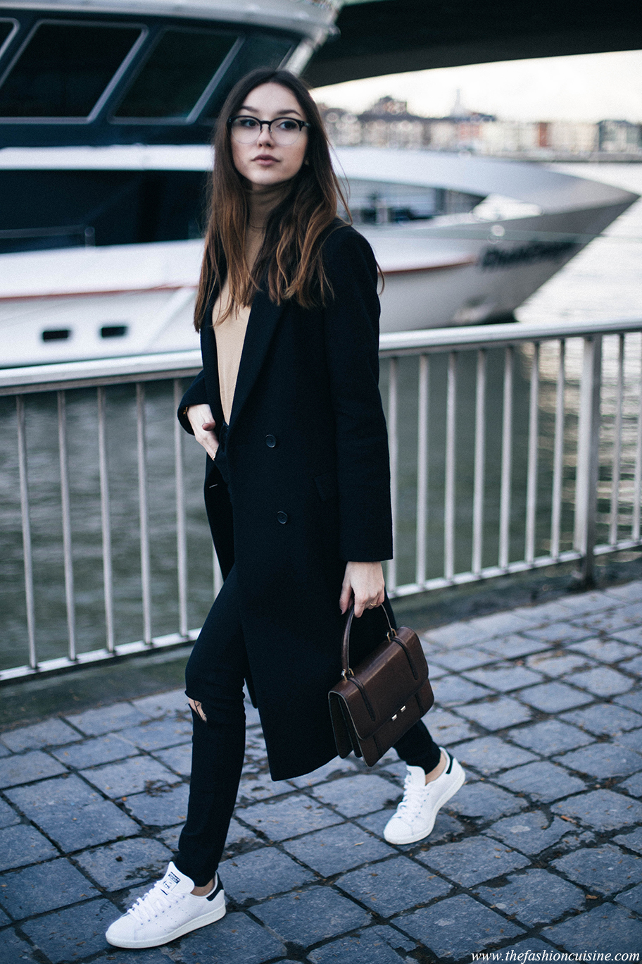 Beatrice Gutu is looking classy and sophisticated in a long black overcoat, paired with skinny distressed denim jeans and white sneakers. A miniature satchel will add the authenticity everyone wants in a winter look! Coat: Maison Scotch, Turtleneck: Zara, Jeans: Asos, Sneakers: Stan Smith.