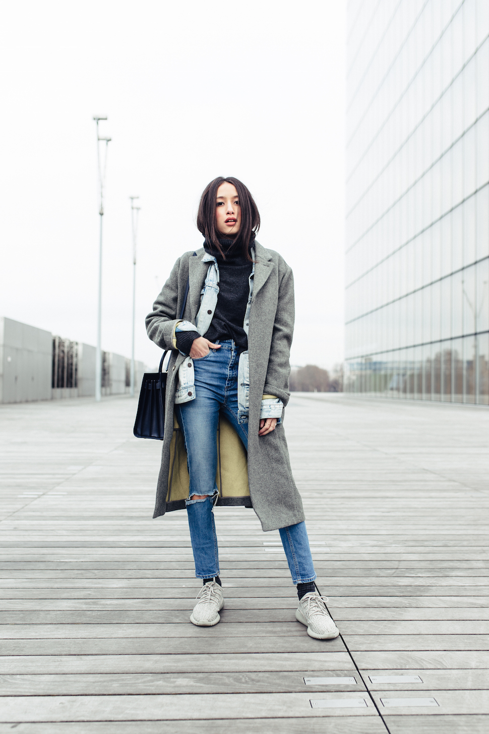 High waisted jeans are an absolute killer trend! Alexandra Guerain rocks a pair of distressed denim jeans as part of a cute winter outfit featuring a grey maxi coat and black rollneck top. Outfit: Asos.