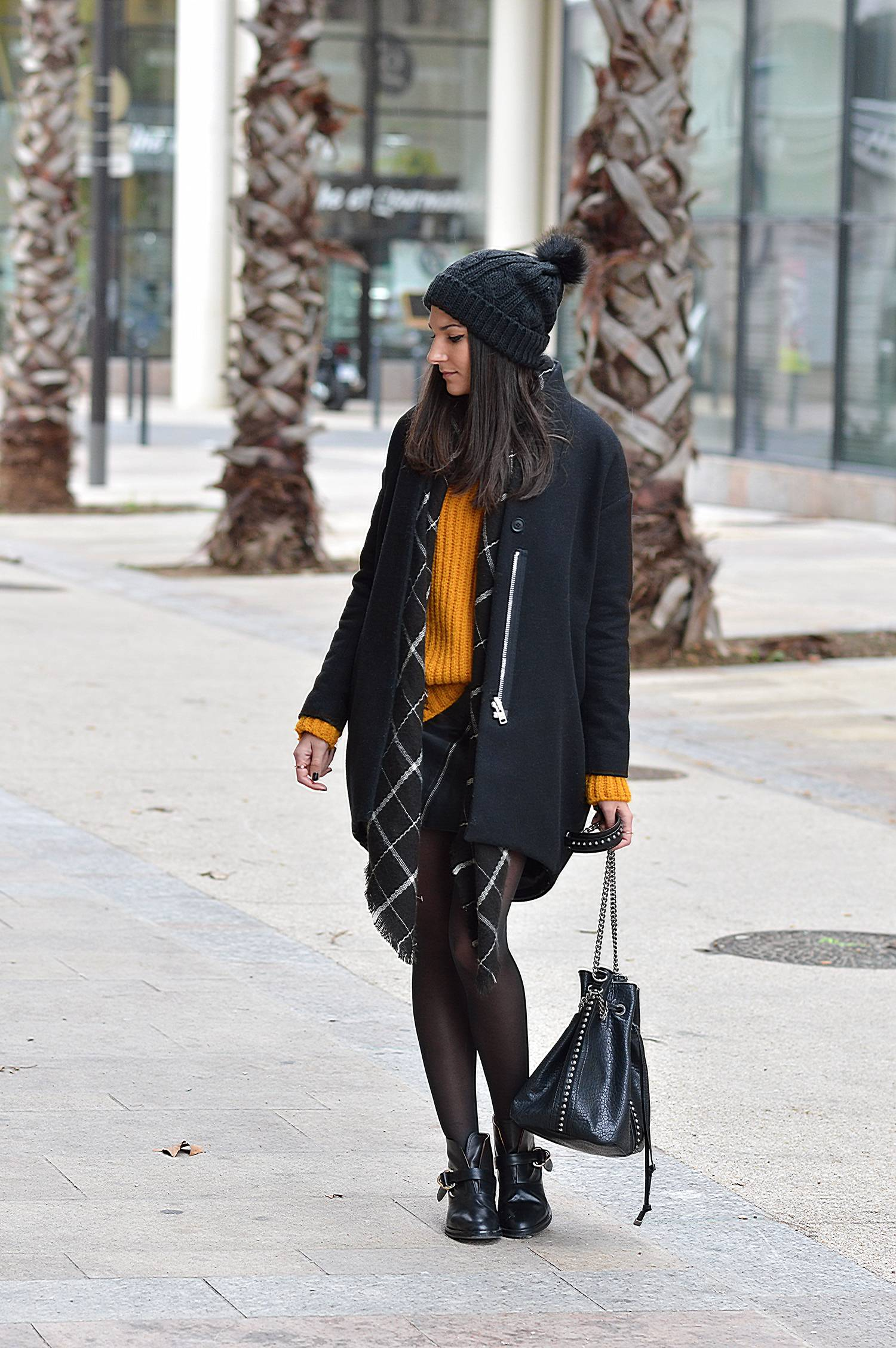 Dare to wear mustard yellow this winter! Federica L. shows how to wear the look, pairing a mustard knit sweater with a simple skirt and overcoat. The knitwear accessories are also a must for a classic winter style. Coat/Boots: & Other Stories, Sweater/Skirt/Hat: Mango.