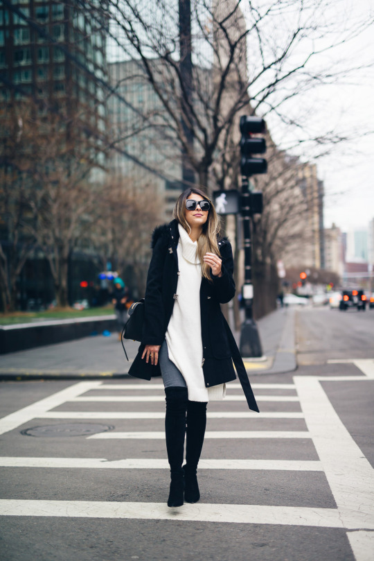 Oversized knitwear is a new and upcoming trend! Pam Hetlinger wears this sleek and stylish cream long knit sweater over grey denim and with a pair of thigh high boots. Coat: Nordstrom/Jeans, Boots: Delman.