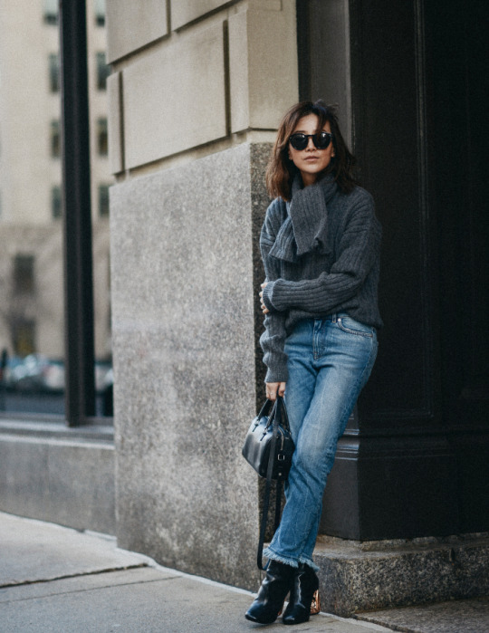Diana Z Wang is staying both chic and warm in this gorgeous winter ensemble consisting of a scarf-tie, matching sweater, jeans and ankle boots. A mini handbag like this one is always a good choice too! Scarf/Sweater: J.W. Anderson, Jeans/Boots: Acne Studios, Bag: Saint Laurent.