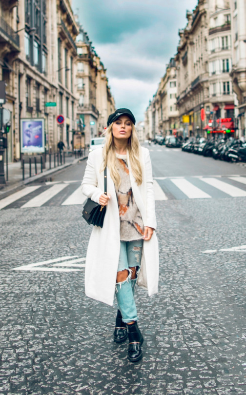 Angelica Blick's cute winter outfit consists of a gleaming white maxi coat, heavily distressed denim jeans, and a funky graphic print knitted sweater. Throw in a peaked cap if you really want to rock this cool and edgy style! Knit/Coat: Malene Birger, Jeans: Monki, Boots: Asos.