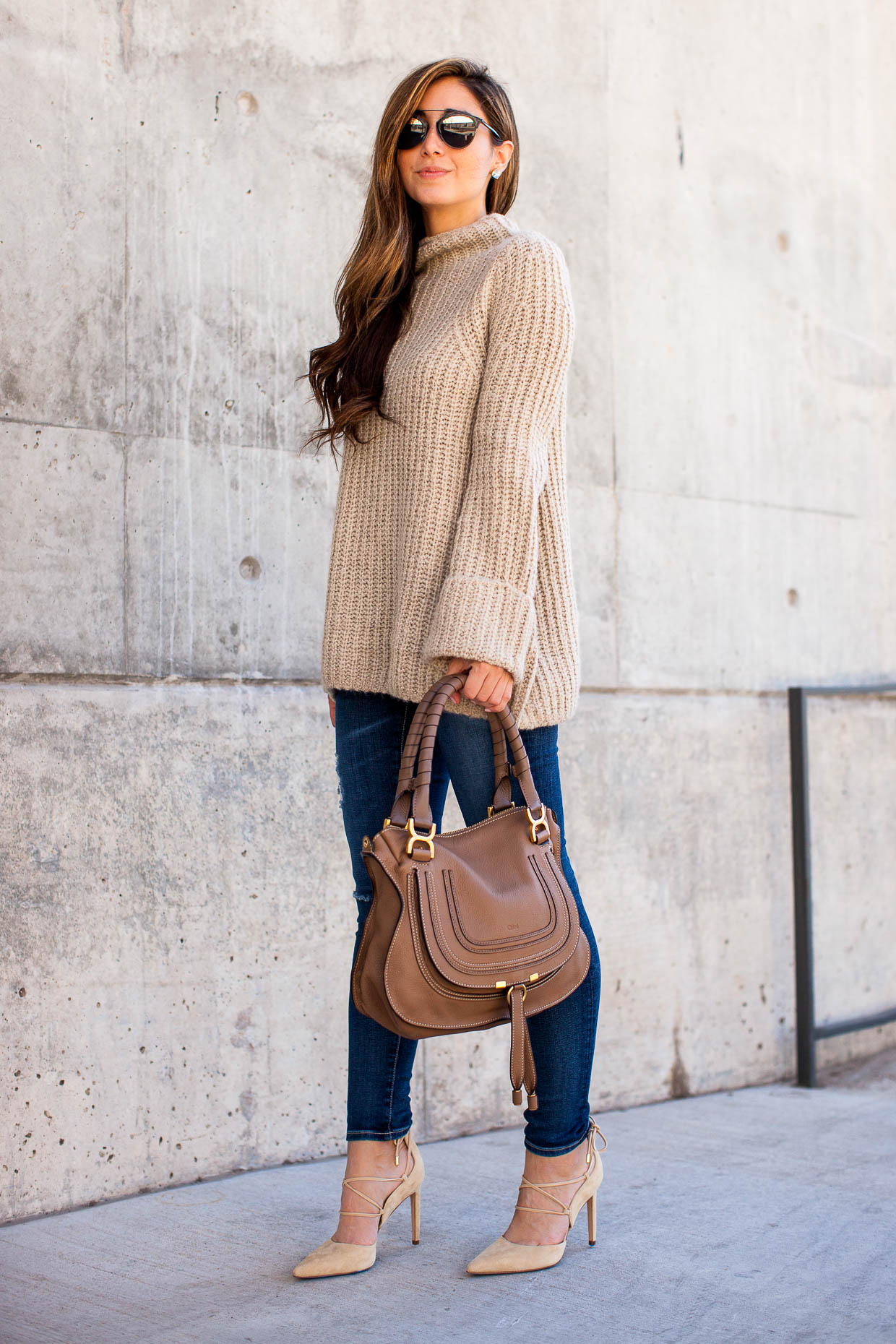 Beige is absolutely the colour of the season! Jessi wears this trendy style on an oversized funnel neck, paired with classic denim jeans and a pair of nude heels. Jumper: Topshop, Shoes: Sam Edelman.