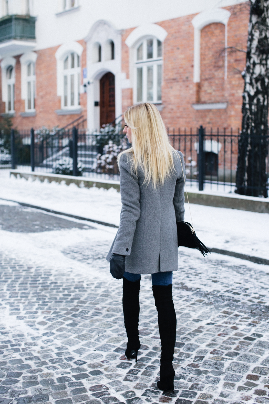 Though perhaps not the most practical choice for the snow, there's no denying that these stunning thigh high boots make Katarzyna Tusk's casual outfit of jeans and a coat ten times more sophisticated; we love it! Bag: Bershka, Shoes/Jeans: Zara, Sweater: Karen Millen, Coat: MLE Collection, Gloves: Cos.