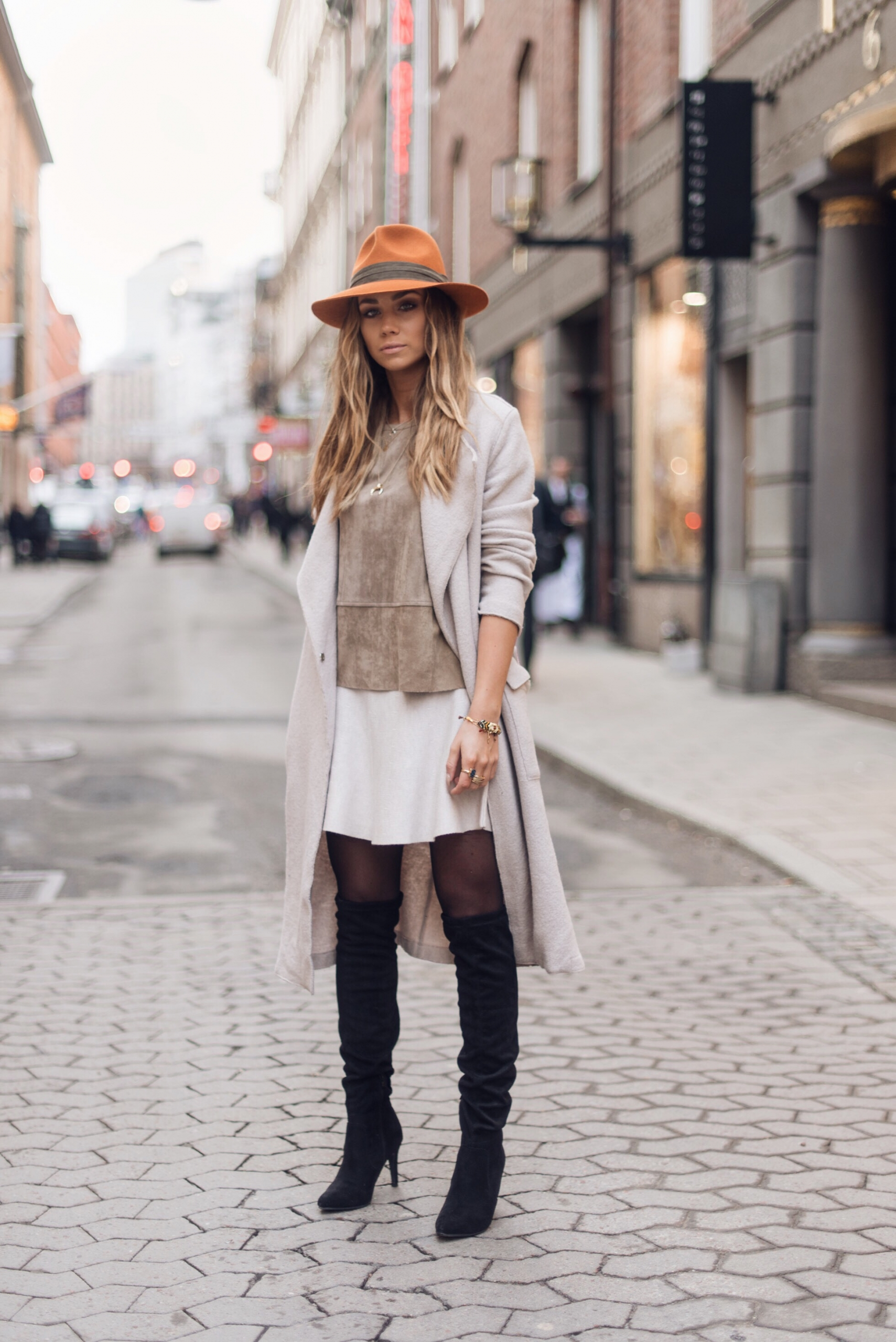 Lisa Olsson shows us how to wear thigh high boots with a skirt through this stylish combination of a cute white skirt and an earthy toned suede top. Wear this look with a statement fedora if you want to recreate Lisa's look exactly! Top: Neo Noir. Skirt: Gina Tricot, Shoes: Din sko, Coat: Filippa K.