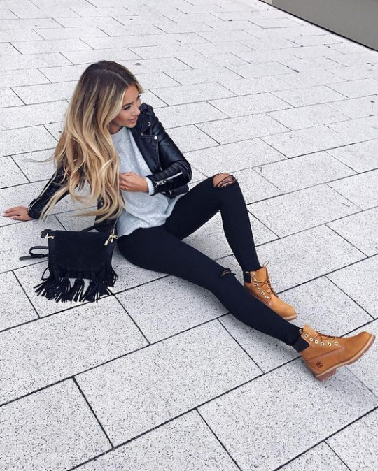 Janine Wiggert styles the classic sandy brown Timberlands with black jeans, a blue sweater, and a leather jacket. We love the combination of leather with this frayed suede cross-body bag.  Bag: Camelia Roma, Shoes: Timberland.