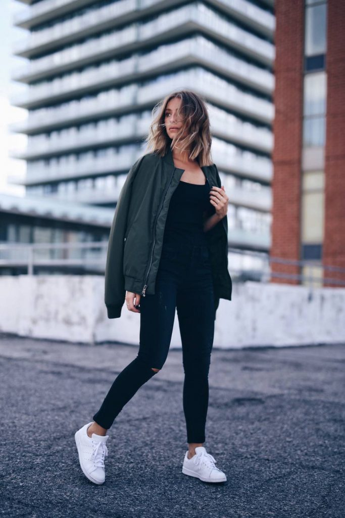 Jill Lansky is wearing a khaki bomber over an all black style consisting of a tank top, high waisted jeans, and bright white sneakers to provide the ultimate contrast.   Jeans: Express, Top: One Eleven, Bomber Jacket: Express, Sneakers: Adidas.