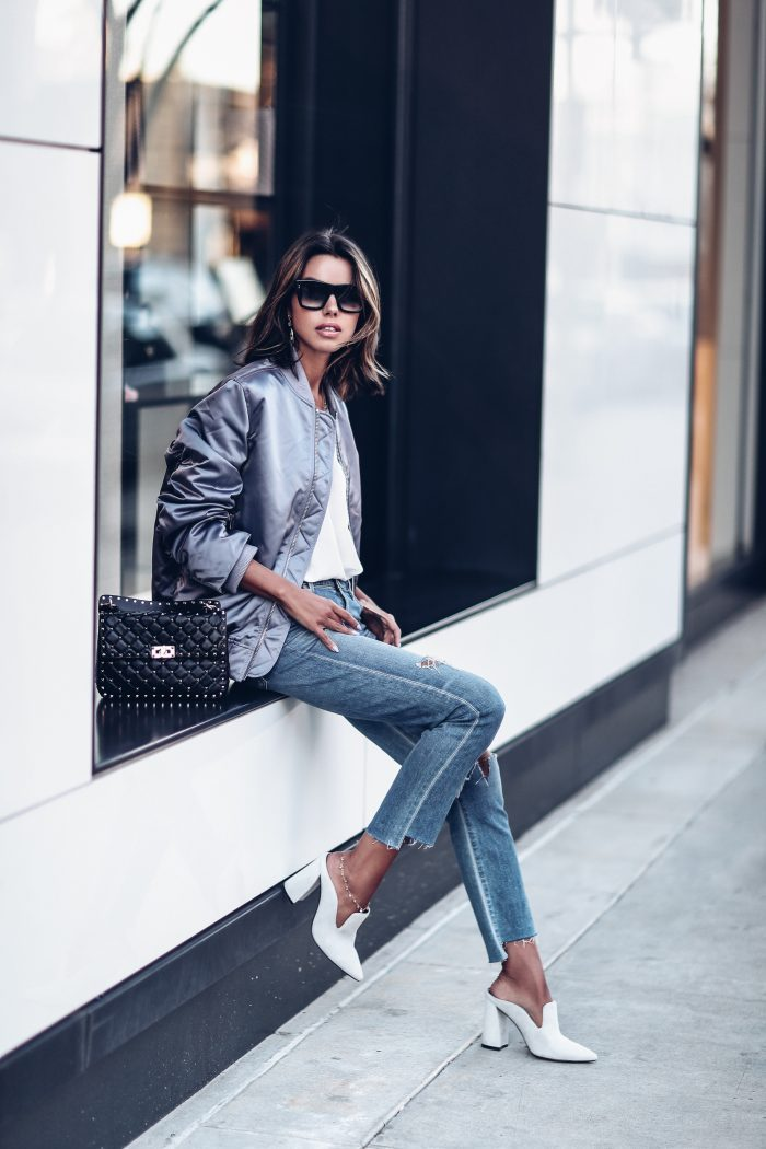 Annabelle Fleur has created a super sleek casual style here, pairing this metallic silver bomber with a white tee and cropped denim jeans for a retro style we adore! Pair a look such as this with edgy chunky mules to authentically capture Annabelle's look. Mules: Marc Fisher, Bomber: ACNE, Jeans: Citizen of Humanity.