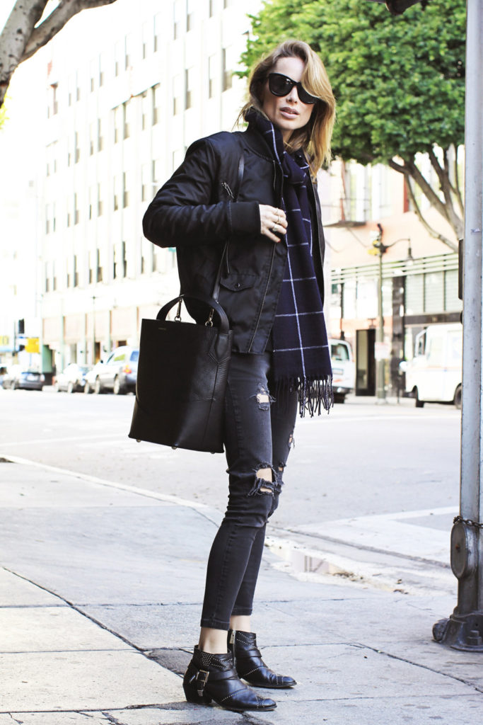 Anine Bing is rocking a monochrome bomber jacket look consisting of edgy studded ankle boots, distressed denim jeans, and a gorgeous statement scarf. We love this look for its simplicity and authenticity.  Outfit: Anine Bing.