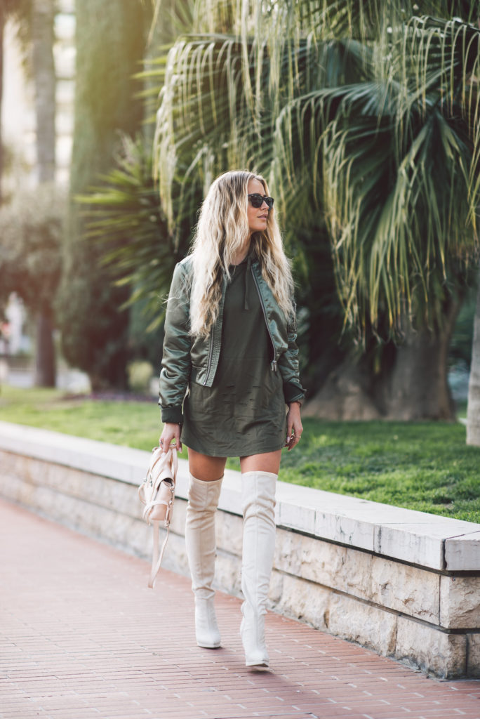 Wondering how to wear a khaki bomber jacket? We recommend wearing the look like Janni Deler by pairing a cropped jacket with a matching khaki hoodie and white thigh high boots.   Jacket: Gina Tricot, Dress: Lmso.com, Bag: Phillip Lim, Shoes: Nelly.