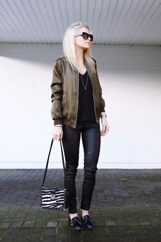 What better way to finish off this casual all black outfit than with a simply stylish khaki bomber jacket? Caroline Daur has created a wonderful everyday style, pairing leather leggings, a printed bag for vibrance, and a silk bomber.   Jacket: Asos, Trousers: Edited, Top: Topshop, Shoes: Zara, Bag: MCM.