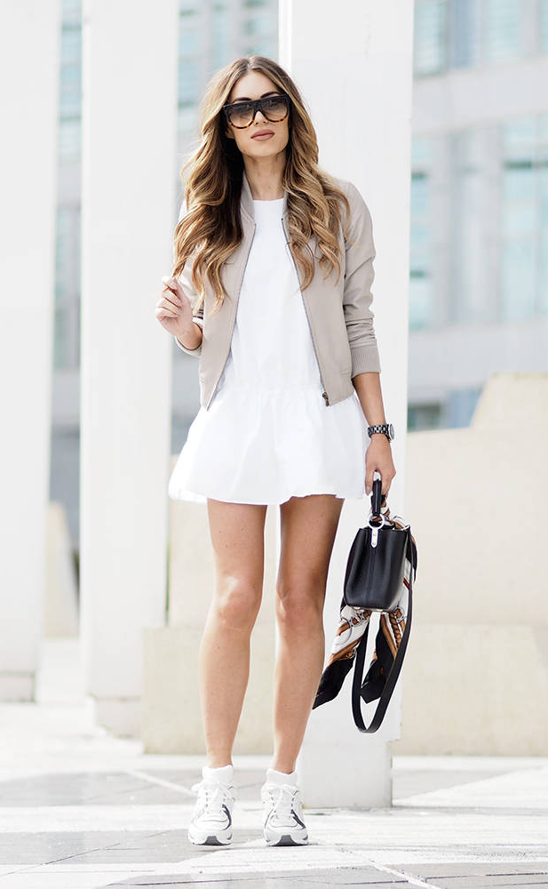 Wear the bomber jacket trend in beige over a white mini dress and with simple sneakers to steal Lydia Lise Millen's winning sporty chic style! Paired with shades and a leather bag, this look is perfect for summer!  Dress: Zara, Jacket: ME+EM, Trainers: Chanel, Scarf: Gucci, Bag: Louis Vuitton.