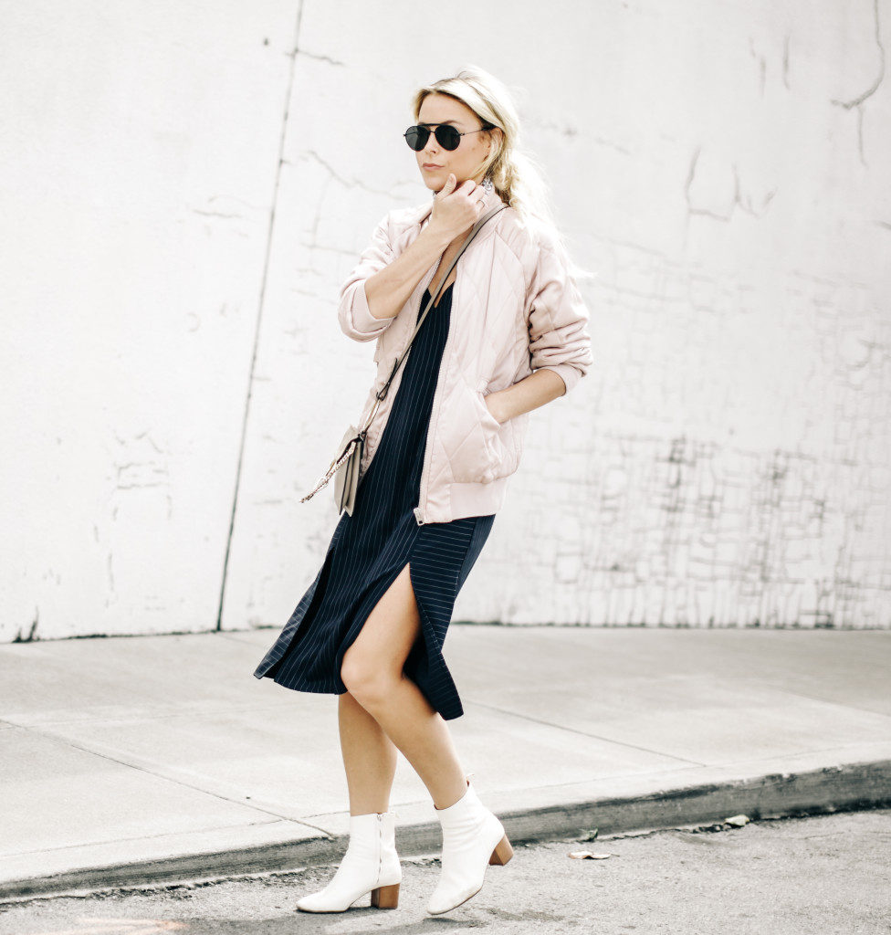 A pale pink bomber like this is perfect for a cute and girly spring style which still retains some edginess! Mary Seng is wearing this look with a slit-detailed midi dress and white Chelsea boots; creating a style we love!   Bomber: Coach, Dress: Topshop, Boots: Isabel Marant.
