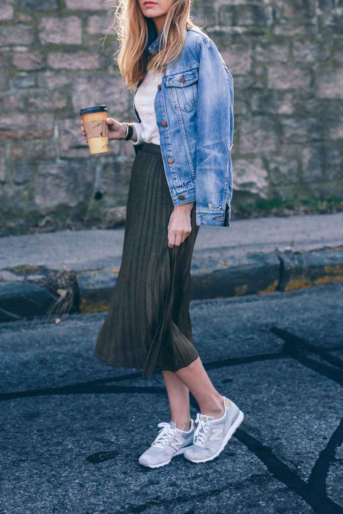 Another great way to style the pleated skirt is to wear it with denim like Jess Ann Kirby. By pairing this bottle green skirt with a faded denim jacket, Jess has added a degree of casual retro chic to her look.   Skirt/Tee: Reiss, Jacket: Madewell, Sneakers: New Balance.
