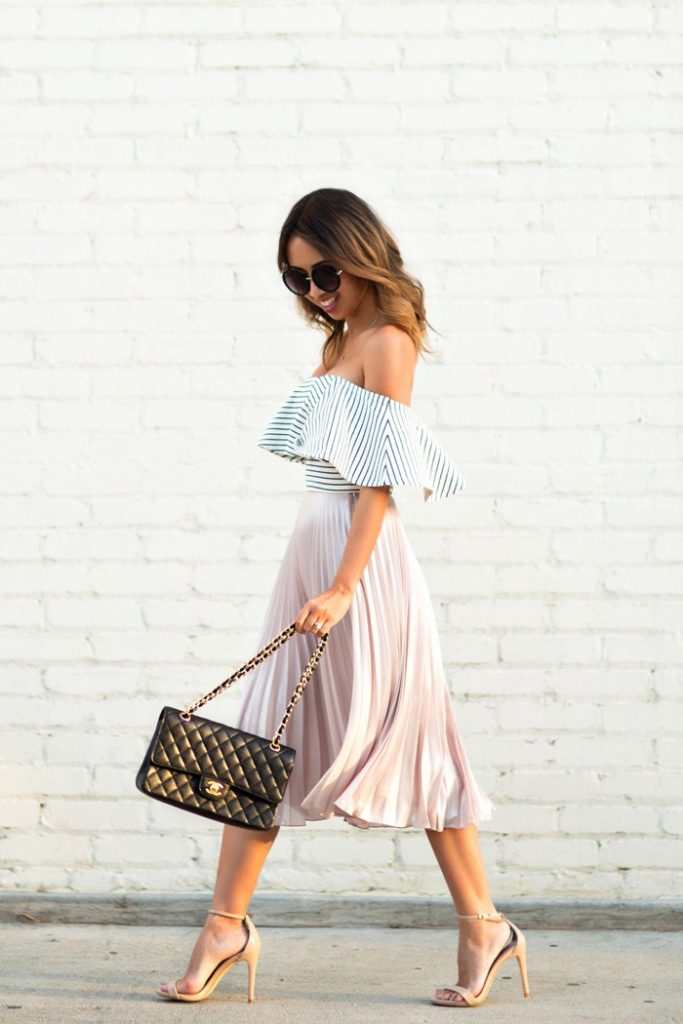 Kim Le has created a gorgeous spring look here by pairing a flowing blush pink pleated skirt with a flirty off the shoulder top with a cute striped pattern. Wear this look with heels to get a glamorous and elegant style.   Pleated Midi Skirt: Topshop, Top: ASOS, Shoes: Steve Madden, Sunglasses: Nordstrom, Handbag: Chanel.
