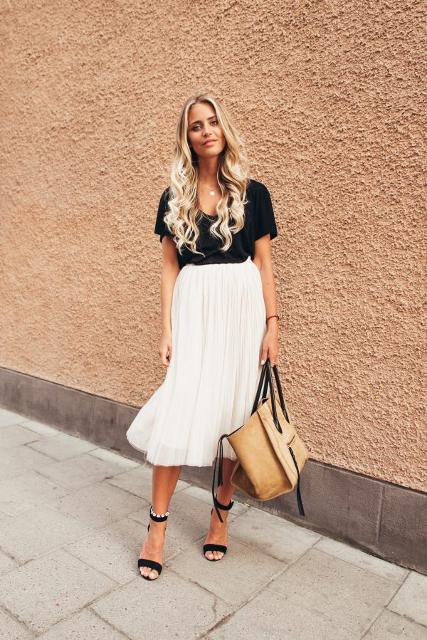 A white flowing pleated skirt like this one is the perfect way to wear this summer's hottest trend! Janni Deler is looking totally striking in this gorgeously contrasting outfit consisting of a white skirt, a black top and sleek black heels. Shirt: Anine Bing, Skirt: From Spain, Shoes: Jennie-Ellen.
