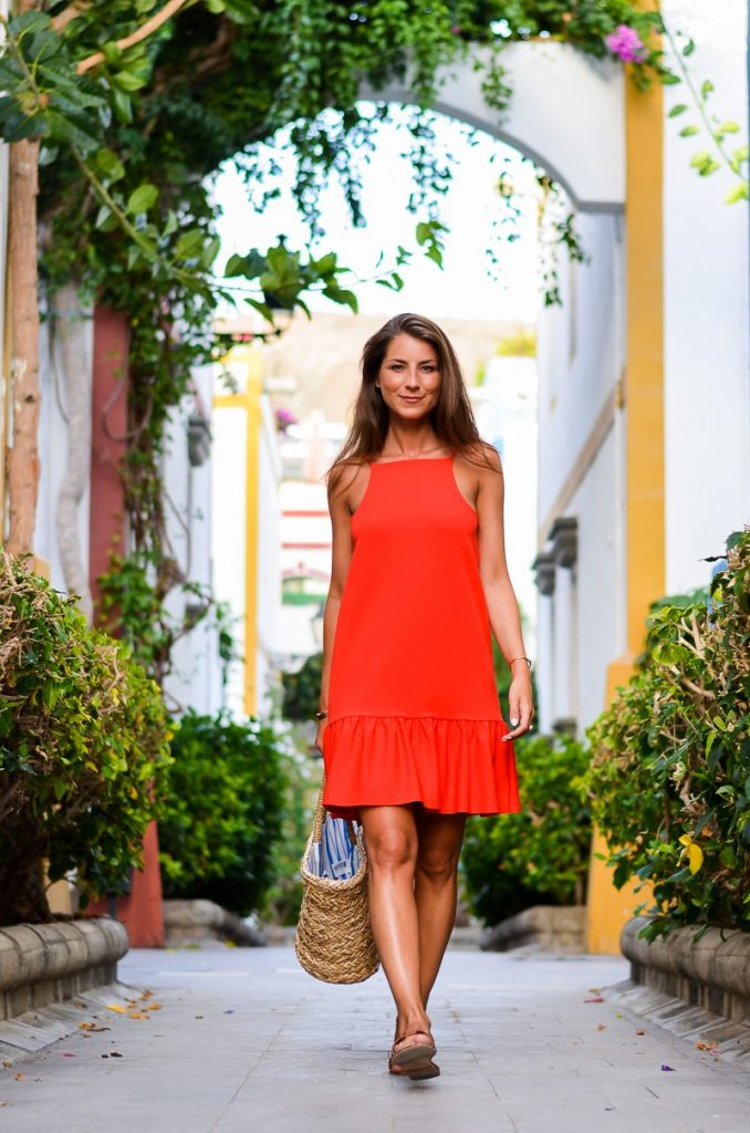 Stephanie Van Klev is rocking this striking red dress with pleat detailing, pairing it with simple sandals and a straw bag for an understated and elegant look.   Dress: Zara, Bag: H&M, Sandals: Hermès.