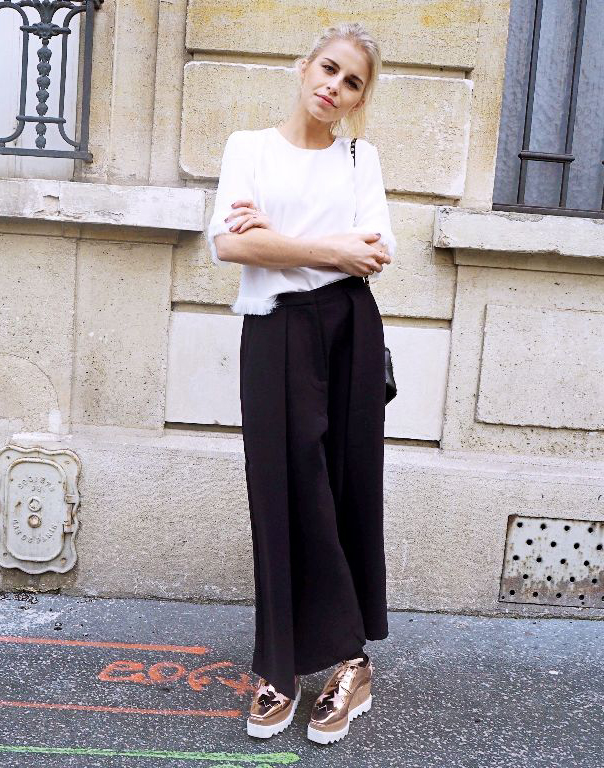 The culottes trend is definitely making a comeback! Caroline Daur wears the look with a simple white top and a pair of awesome metallic platform shoes to create contrast and add some edge to the look. Top/Trousers: Iris and Ink, Shoes - Stella Mccartney, Bag - Valentino.