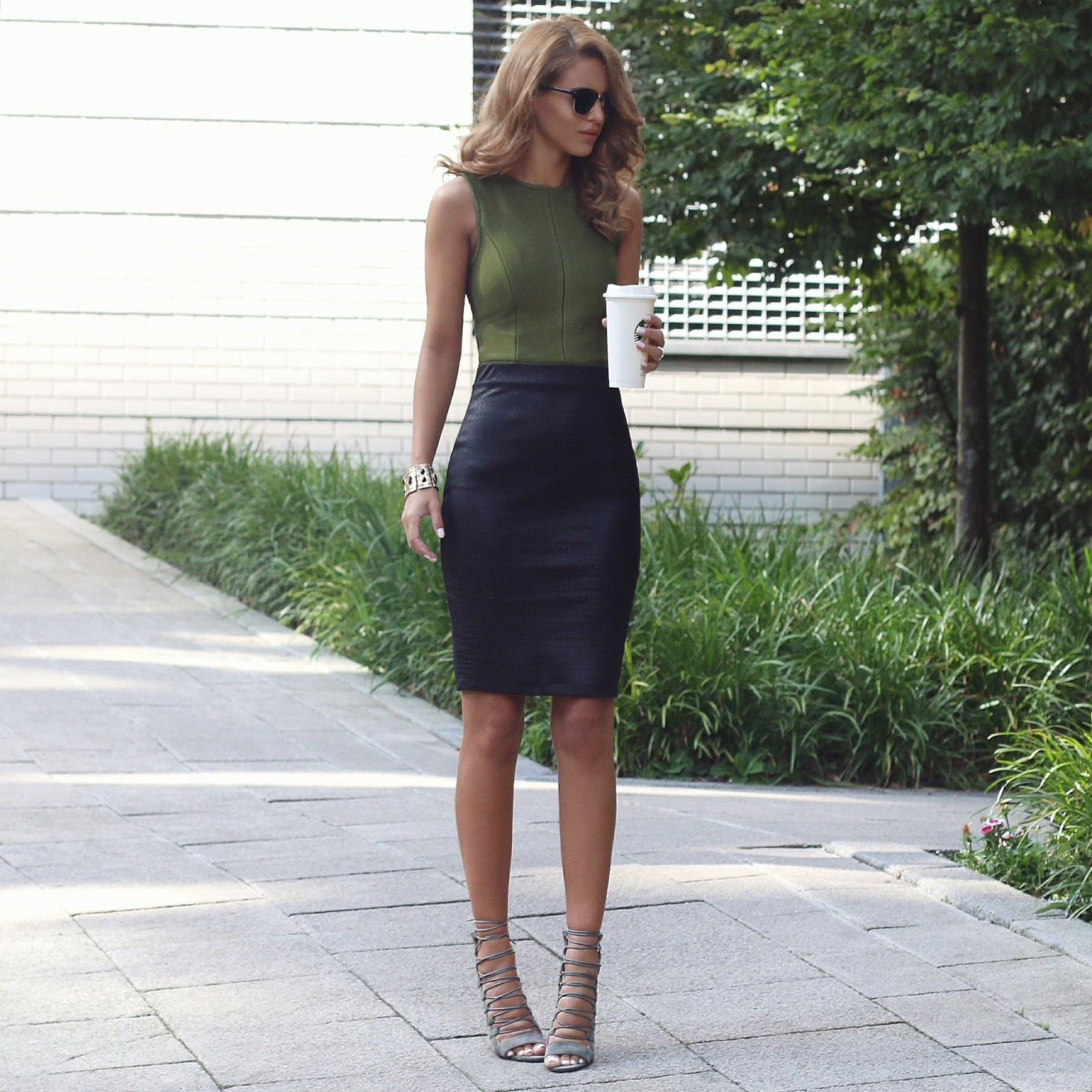 Nada Adelle keeps it simplistic in this spring outfit consisting of a leather midi skirt and a sleeveless khaki vest with matching heels. A skirt like this is inherently figure hugging and is therefore a great way to show off your curves! Top: My Bandage Dress, Skirt: Loft, Heels: Public Desire.