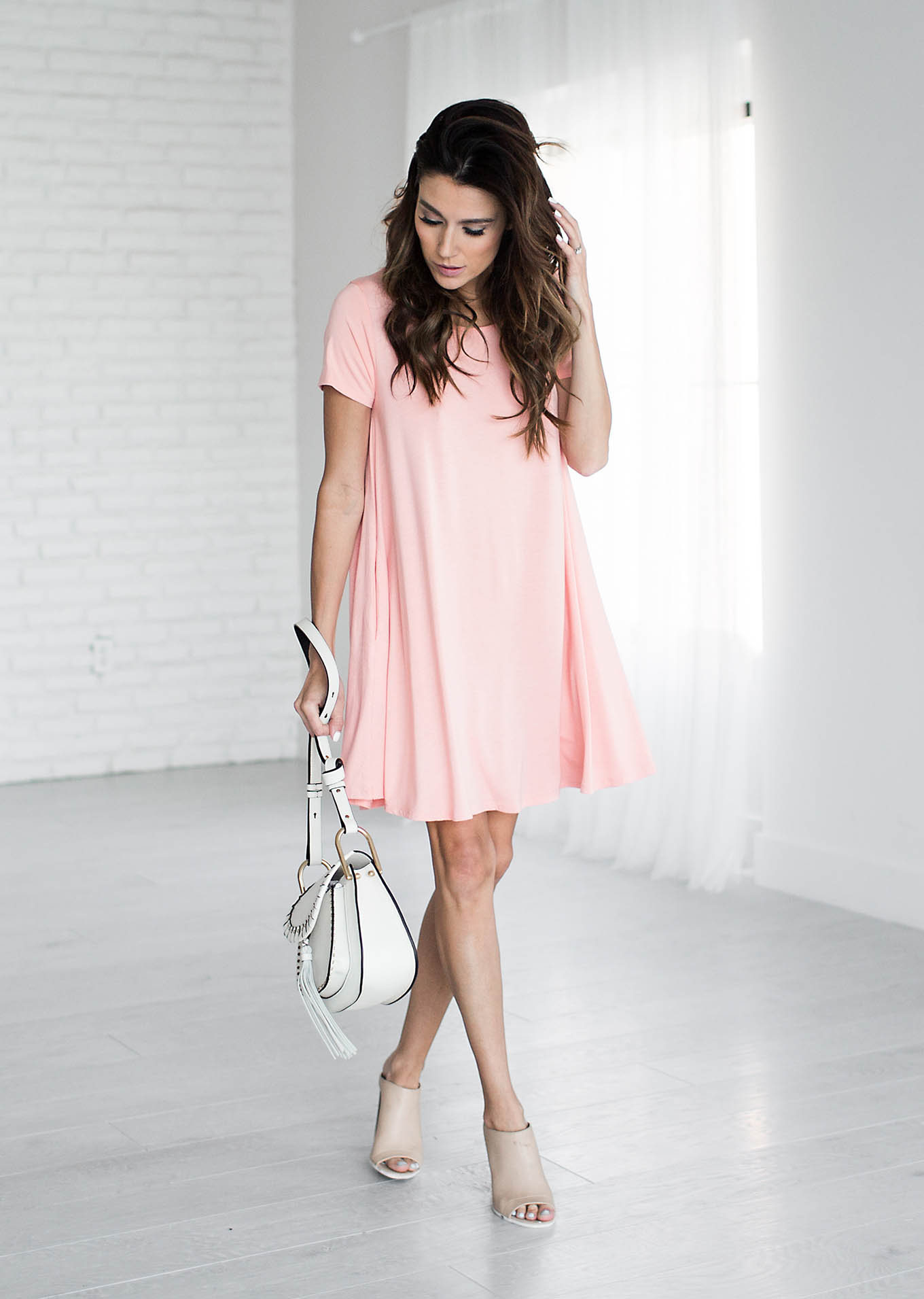 Christine Andrew is keeping it stylishly minimalist here, wearing a simply styled pink t-shirt dress with nude sandals and a white handbag. This look is ideal as it is both affordable and completely achievable! Dress: ILY Couture.