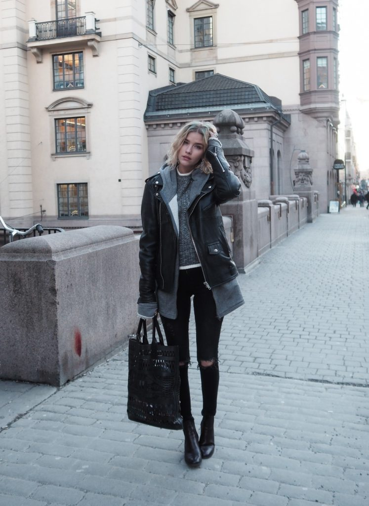 Elsa Ekman rocks a simple yet edgy fall style here, pairing a knitted sweater, a hoodie, and an oversized leather jacket together with distressed jeans. We love this style; especially worn with leather boots and a matching bag!  Jacket: Deadwood, Jeans: Cheap Monday, Boots: Feet First, Bag: DAY Birger et Mikkelsen.