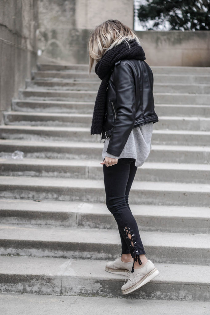Camille Callen wears the leather jacket trend with a pair of alternative style lace up jeans and a knit scarf here, creating a trendy and edgy monochrome look.   Top: Zara, Jacket: Princesse Tam Tam, Jeans: Mango.