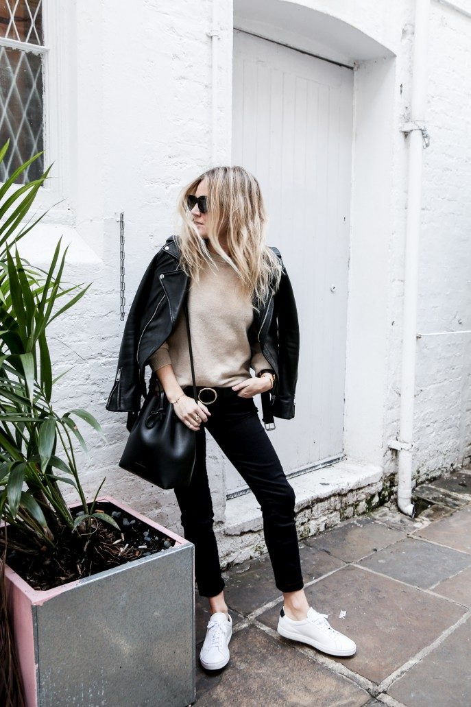 A leather jacket will always go a treat over a knitwear sweater. Lucy Williams looks classy and cool in this simple combination of a beige sweater, black trousers, and a pair of white sneakers. Jumper/Jeans: AG, Belt: Frame, Trainers: Common Projects, Bag: Mansur Gavriel, Sunglasses: Celine.