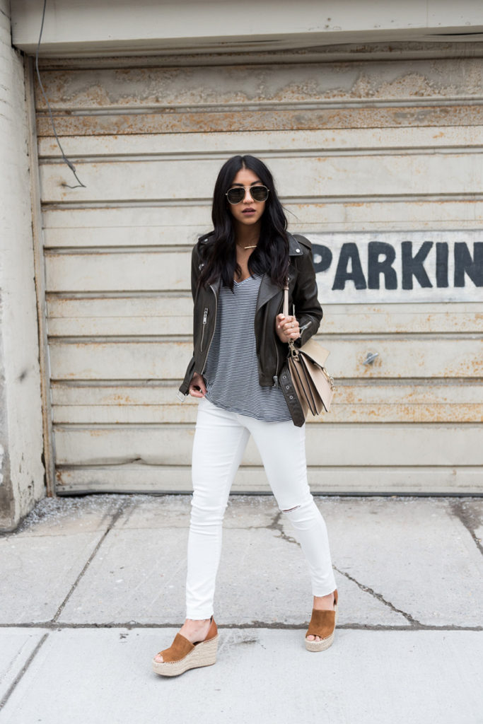 Kayla Seah looks super glam in this authentic leather jacket and white jeans combination. The stark contrast between the white and leather evokes cool and edgy vibes, and by pairing this look with wedges Kayla has created a stylish overall look!  Jacket: All Saints, T-Shirt: Zara, Jeans: Levi's, Wedges: Marc Fisher, Bag: Chloe.