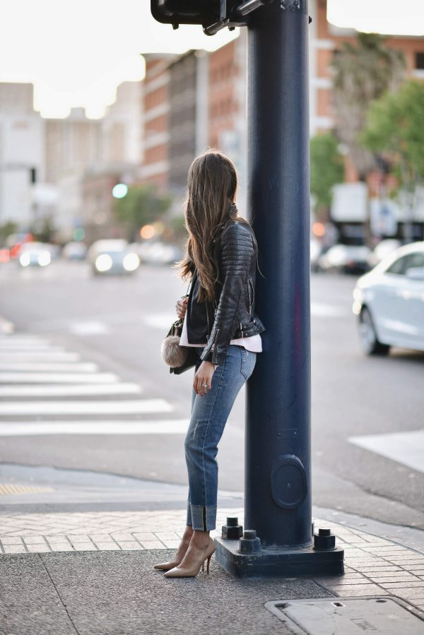 Wearing a leather jacket with heels is a sure fire way to get yourself a sexy yet sophisticated look! Paola Alberdi is absolutely owning this outfit, consisting of denim jeans rolled at the ankle with nude heels, a white blouse and a classic biker jacket. Jacket: All Saints, Jeans: Zappos.