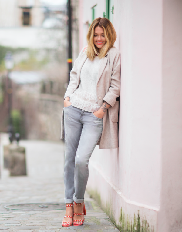 Caroline Receveur has gone all out neutral in this stylish combination of grey jeans, a cream ruffle top and a matching off-white overcoat. Break up the outfit with a pair of red studded heels to steal Caroline's spring style! Brands not specified.