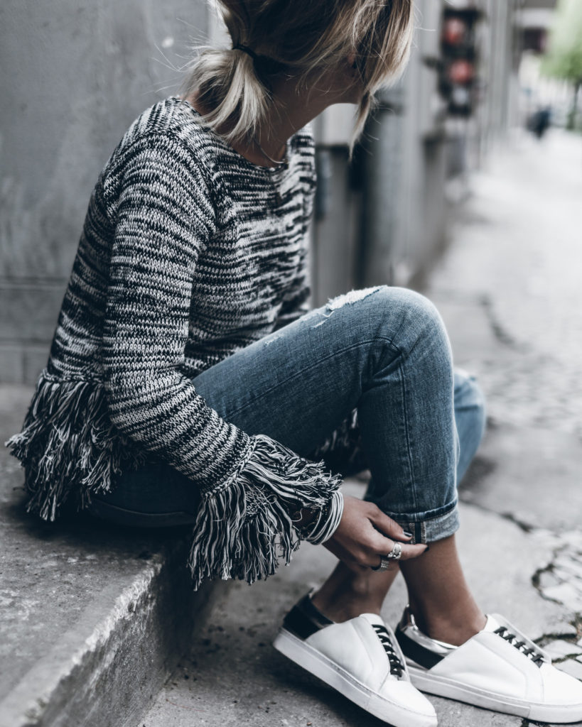 A fringed knit sweater is a great way to wear the spring knitwear trend! This piece is ultra alternative, with fray detailing at the sleeves and waist to create a snazzy overall style! Via Jacqueline Mikuta.  Brands not specified.