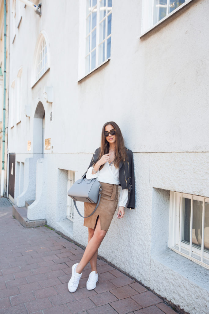 Kenza Zouiten has created a sophisticated spring style here by pairing a cute suede slit-detailed skirt with a white wrap around blouse and a cropped leather jacket. Pair this style with fresh white sneakers to get that casual vibe.   Jacket: Ivyrevel, Blouse: H&M, Skirt: Twist & Tango.