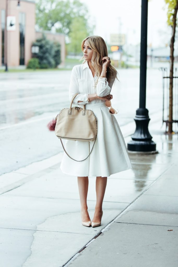 An all white look is a sure way to achieve a gorgeous, feminine spring style. Cara Loren looks utterly entrancing in this simple but intricate style consisting of an A line skirt and a white blouse.   Skirt: H&M, Shirt: Rachel Parcell.