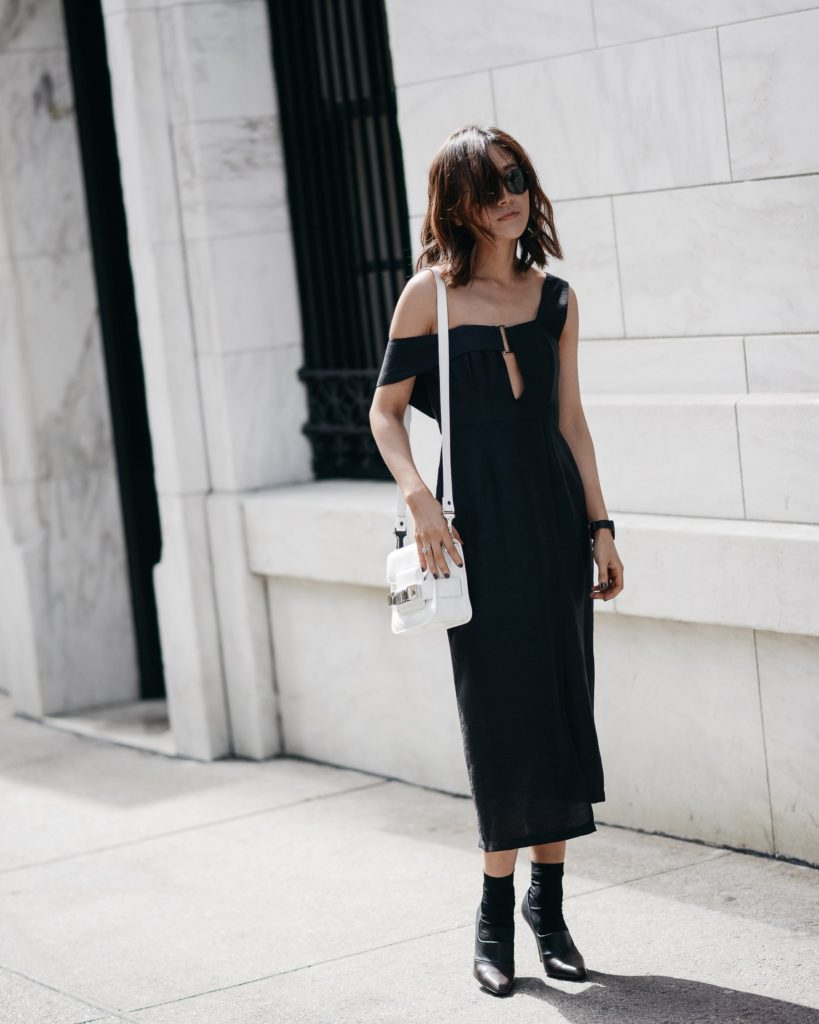 Diana Z Wang is looking striking in this ultra elegant off the shoulder black midi dress, worn with a simple contrasting white mini satchel and a pair of leather heeled boots. A dress like this is great for dressing up or just hitting the streets!  Dress: Third Form, Pumps: Stella McCartney, Bag: Proenza Schouler.