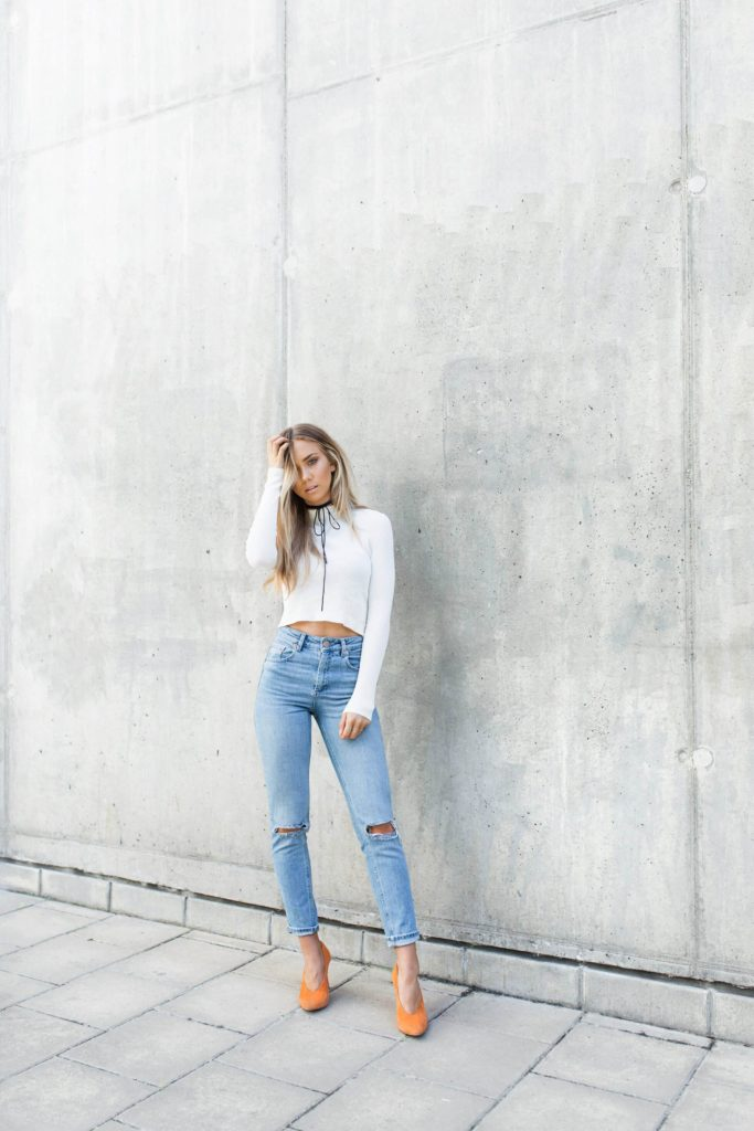 Lisa Olsson has opted for a classic casual style here, wearing a pair of ripped denim jeans with a cropped white sweater and a pair of glammy orange heels for added edge.   Top: H&M, Jeans/ Neck Tie: ASOS, Shoes: Jennie-Ellen.