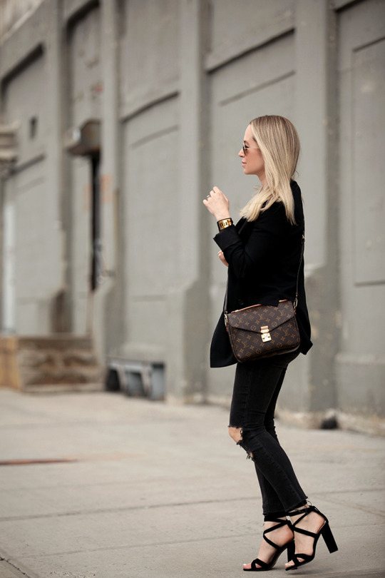 Helena Glazer is rocking a smart casual style here, pairing distressed black jeans with an oversized blazer and a pair of statement platform heels. An all black look such as this will always afford you a ready-to-go style!   Tee: Elliot, Denim: Rag & Bone, Sandals: Steve Madden Christey. Choker: HRH Collection, Bag: Louis Vuitton.