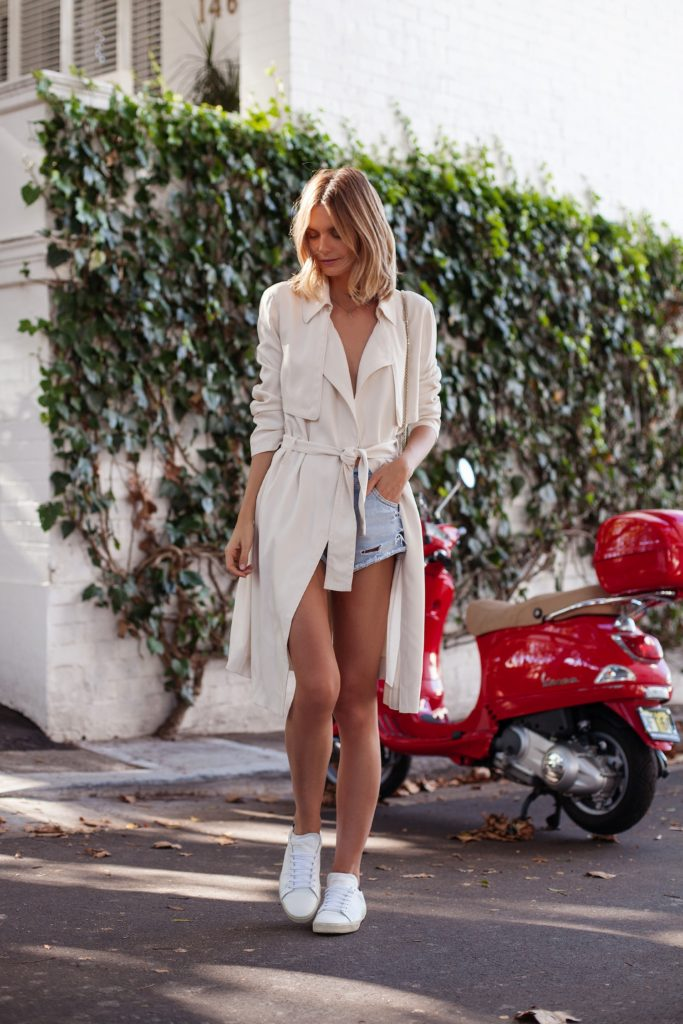 Wear a trench with shorts for the ultimate summer style. Jessica Stein looks cute and casual in these washed out denim shorts, simple sneakers, and a beautiful cream trench.   Coat: Sportscraft, Shorts: Mango, Sneakers: Saint Laurent, Bag: Valentino Rockstud.